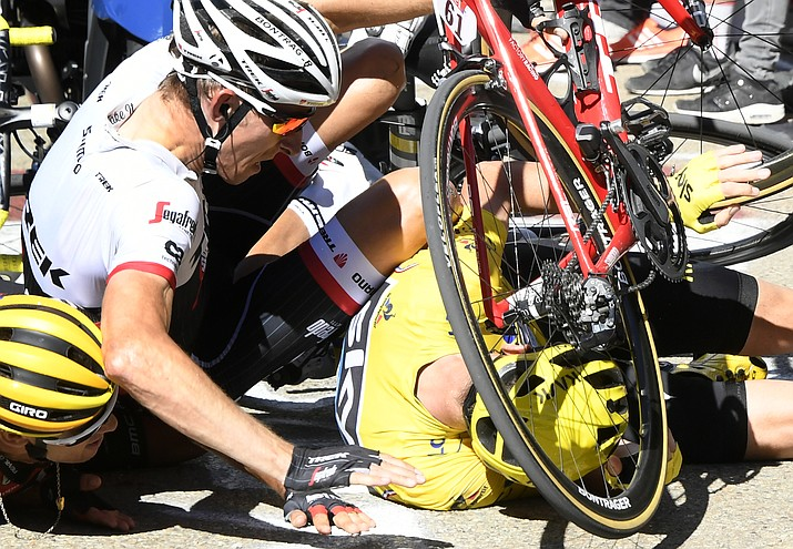 """Britain's Chris Froome, wearing the overall leader's yellow jersey, right, Netherlands' Bauke Mollema, center, and Australia's Richie Porte crash at the end of the 12th stage of the Tour de France cycling race with start in Montpellier and finish six kilometers (3.7 miles) before the Mont Ventoux, France, Thursday, July 14. The wind, combined with a temperature just above the freezing level on top of the """"Giant of Provence,"""" forced organizers to move the finish line."""