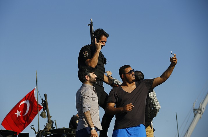 A Turkish man takes a selfie with a Turkish police officer, loyal to the government, as they stand atop tanks abandoned by Turkish army officers, against a backdrop of Istanbul's iconic Bosporus Bridge, Saturday, July 16, 2016. Turkish President Recep Tayyip Erdogan told the nation Saturday that his government is in charge after a coup attempt brought a night of explosions, air battles and gunfire across the capital that left dozens dead.