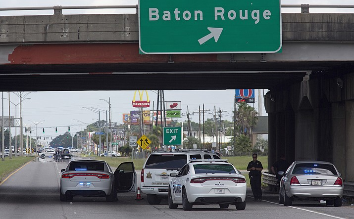 Baton Rouge Police block Airline Highway after police were shot in Baton Rouge, La., Sunday, July 17.  At least three officers are confirmed dead and at least three others wounded after the shooting, a sheriff's office spokeswoman said Sunday. One suspect is dead and law enforcement officials believe two others are still at large, the spokeswoman said.