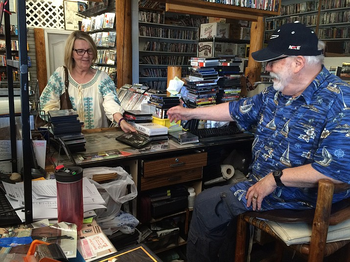 Randy Rodgers, owner of Show Business Video Library, laughs while chatting with his customer Linda Swenson.