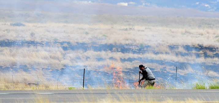 Passersby help to extinguish a wildland fire on Fain Road just south of Lakeshore Drive in Prescott Valley Tuesday afternoon. (Les Stukenberg/The Daily Courier)