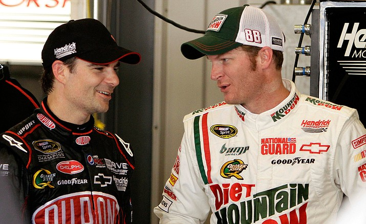 Drivers Jeff Gordon, left, and Dale Earnhardt Jr., talk in the garage area during a practice session for their Sprint Cup Series auto race at the Kentucky Speedway in Sparta, Ky., Thursday, July 7, 2011.