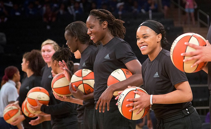 Members of the New York Liberty basketball team await the start of a game against the Atlanta Dream, in New York. The WNBA has fined the New York Liberty, Phoenix Mercury and Indiana Fever and their players for wearing plain black warm-up shirts in the wake of recent shootings by and against police officers. All three teams were fined $5,000 and each player was fined $500. While the shirts were the Adidas brand - the official outfitter of the league - WNBA rules state that uniforms may not be altered in any way.
