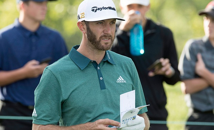 Dustin Johnson checks his yardage book during the Pro-Am for the Canadian Open golf tournament at Glen Abbey in Oakville, Ontario, Wednesday, July 20.