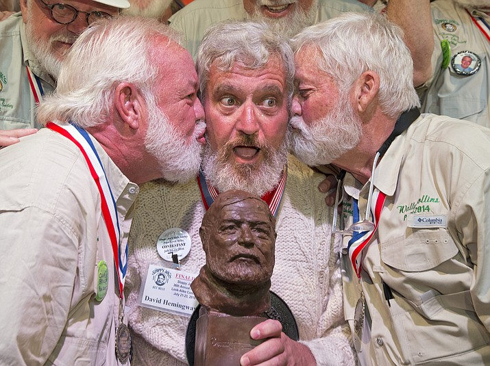 "Dave Hemingway, center,  receives smooches from Charlie Boise, left, and Wally Collins, right, after Hemingway won the 2016 Ernest ""Papa""  Hemingway Look-Alike Contest in Key West, Fla. Success for Dave Hemingway came on the Macon, N.C., resident's seventh attempt to win the coveted title at Sloppy Joe's Bar. Dave Hemingway is not related to Ernest Hemingway, who lived and wrote in Key West in the 1930s."