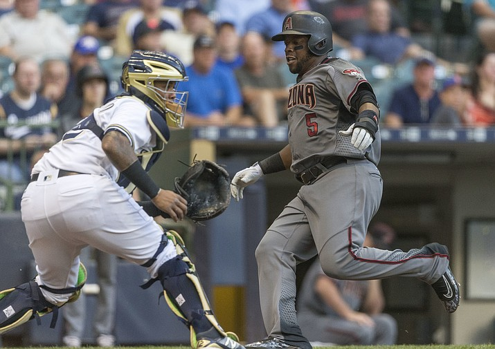 Milwaukee Brewers' Martin Maldonado waits for the throw as Arizona Diamondbacks' Rickey Weeks is able to get past and score during the fourth inning of a baseball game Monday, July 25, in Milwaukee.