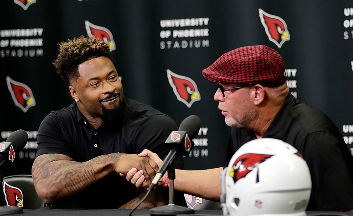Darnell Dockett shakes hands with head coach Bruce Arians, right, after signing a contract with the Arizona Cardinals, Monday, July 25, in Tempe. Dockett, who spent 11 seasons in Arizona, signed a one-day contract so he could retire as a Cardinal.