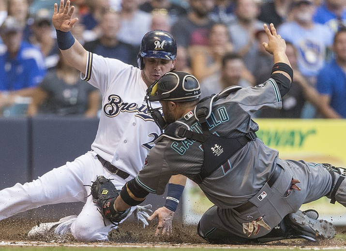 Milwaukee Brewers' Scooter Gennett is tagged out by Arizona Diamondbacks' Welington Castillo during the first inning of a baseball game Tuesday, July 26, in Milwaukee.