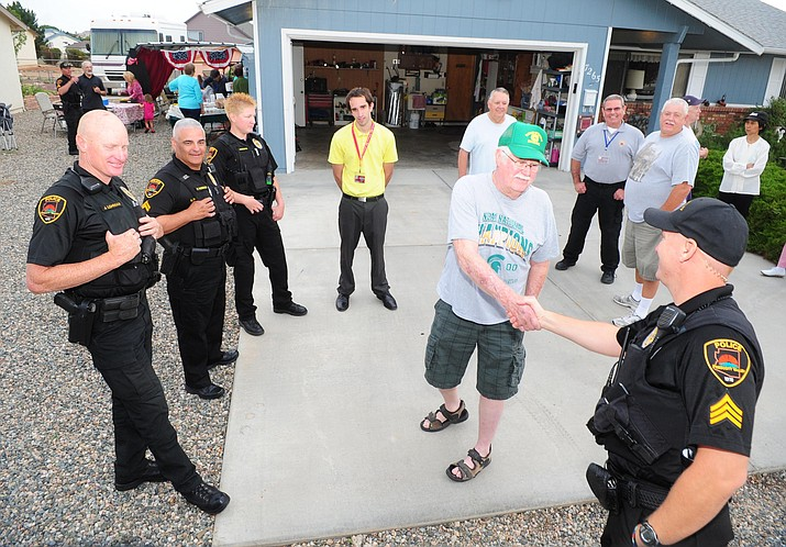 Lou Hartsuff greets Prescott Valley Police officers who stopped by the National Night Out gathering at the Dyke's house on Manley Drive in 2013. This year's National Night Out is Tuesday, Aug. 2.
