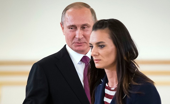 Russian President Vladimir Putin, left, smiles after Russia's pole vaulter Yelena Isinbayeva spoke at the Kremlin, in Moscow, Russia, Wednesday, July 27, during a reception for the Russia's Olympics team. At least 105 athletes from the 387-strong Russian Olympic team have been barred from the Rio Games in connection with the country's doping scandal.