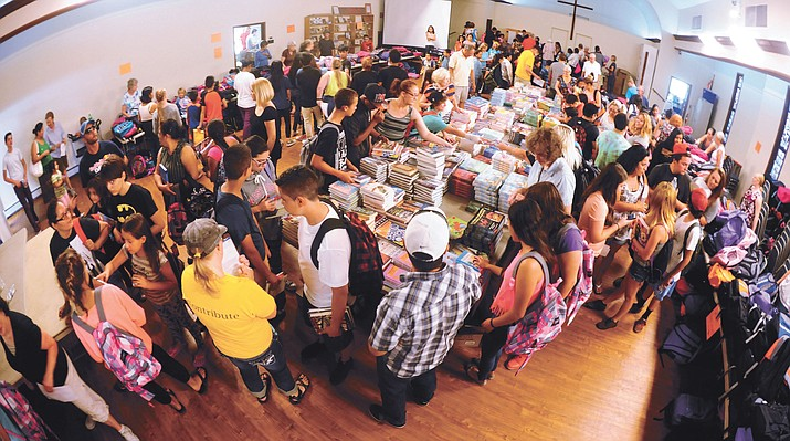 Coalition for Compassion and Justice volunteers hand out 1,400 backpacks filled with school supplies as part of their Fair Start program Saturday in Prescott.