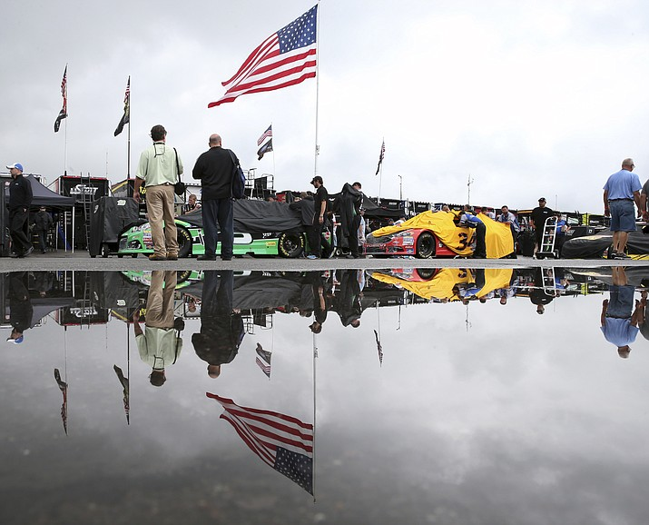 Race cars are lined up for inspection in the rain in the garage area at Pocono Raceway before the NASCAR Sprint Cup Series Pennsylvania 400 auto race Sunday, July 31, in Long Pond, Pa.