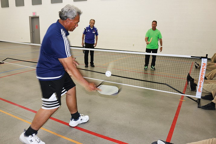Ben Sialega, left, along with teammates Jerry Northwood and J.T. Schulze, demonstrates pickleball earlier this month during a visit to the center.