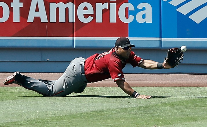 Arizona Diamondbacks left fielder Yasmany Tomas dives but cannot catch an RBI double by Los Angeles Dodgers' Yasiel Puig during the fifth inning in Los Angeles, Sunday, July 31. The Dodgers won 14-3.