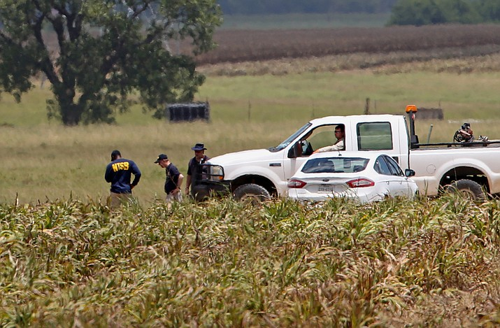 Investigators work the scene of Saturday's hot air balloon crash near Maxwell, Texas, Sunday, July 31. A hot air balloon made contact with high-tension power lines before crashing into a pasture in Central Texas, killing all on board, according to federal authorities who are investigating the worst such disaster in U.S. history.