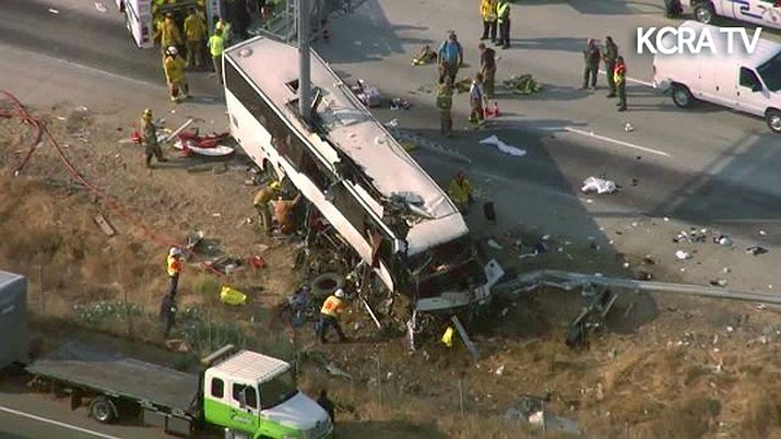 This still frame from video provided by KCRA3-TV shows authorities investigating the scene of a charter bus crash on northbound Highway 99 between Atwater and Livingston, Calif., Tuesday, Aug. 2, 2016. The bus veered off the central California freeway before dawn Tuesday and struck a pole that sliced the vehicle nearly in half, authorities said.