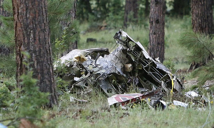 A pile of wreckage sits in the forest just south of Forest Highlands on State Route 89A near Flagstaff, Ariz., early Wednesday morning, Aug. 3, 2016. Authorities say at least one person is dead following the crash of a light plane near Flagstaff Tuesday night.