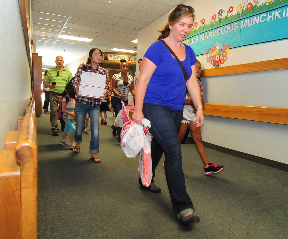 Parents are loaded down with supplies during the first day of the 2016-17 school year at Abia Judd Elementary School in Prescott Thursday morning. (Les Stukenberg/The Daily Courier)