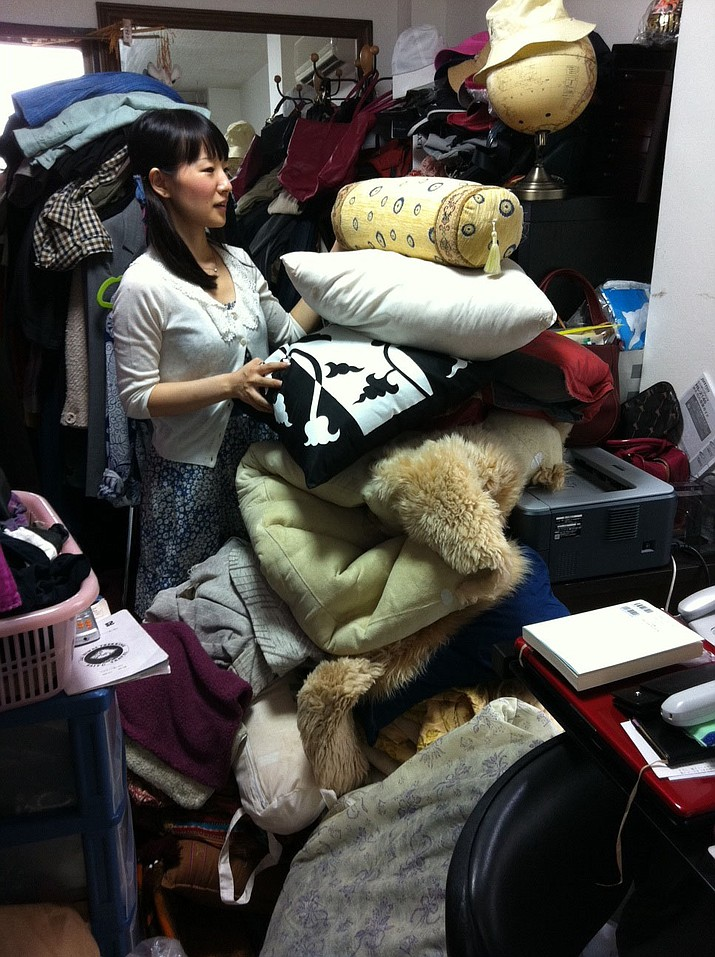 """This undated photo provided by Ten Speed Press shows Marie Kondo working at a client's home to clear away everything that is unneeded in Tokyo, Japan. Kondo is the author of the book, """"The Life-Changing Magic of Tidying Up."""""""