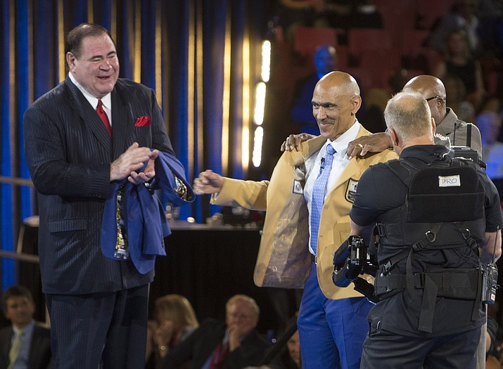 David Baker, left, president of the Pro Football Hall of Fame, applauds as Tony Dungy receives his gold jacket from presenter Donnie Shell at the Pro Football Hall of Fame enshrinees' dinner, Thursday, Aug. 4, in Canton, Ohio.