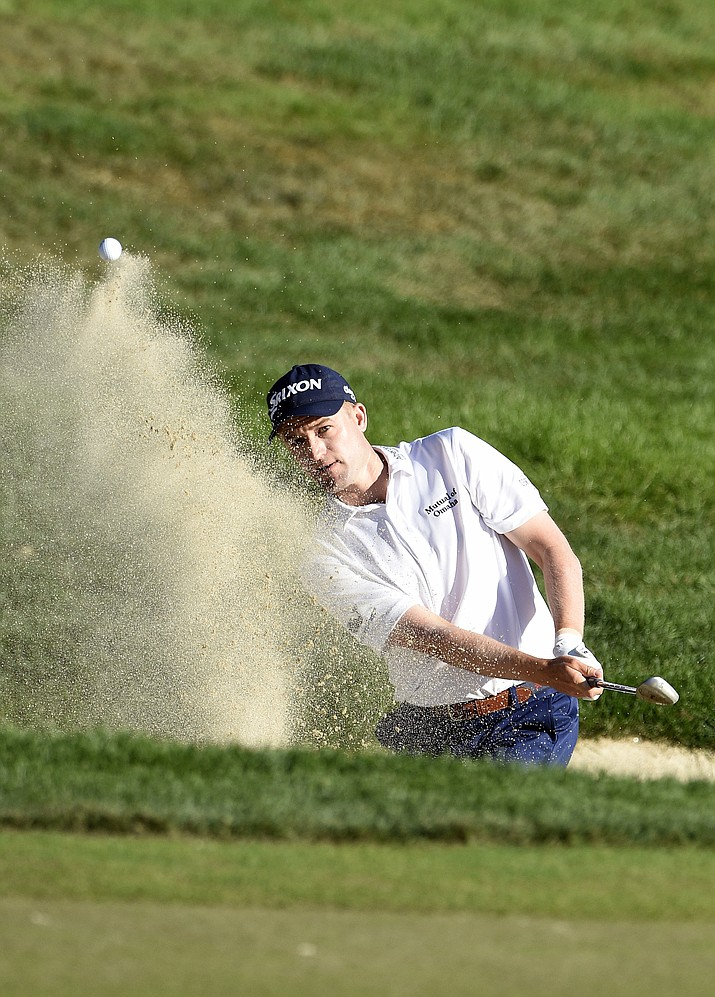 Russell Knox, from Scotland, hits out a greenside bunker on 18th hole during the final round of the Travelers Championship golf tournament in Cromwell, Conn., Sunday, Aug. 7, 2016.