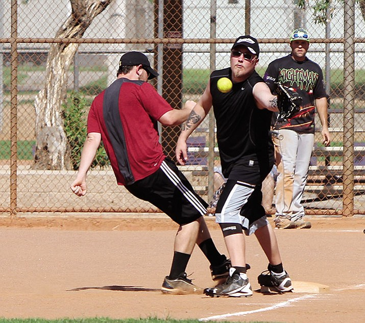 Matt Seppanen of Kingman Crossfit catches the ball as ReMax Team Smith's Kyle Stanford makes it to third during the Fifth Annual John Bathauer Memorial Scholarship Co-ed Softball Tournament at Centennial Park Saturday.