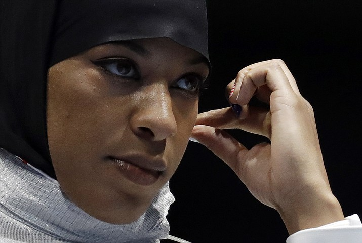 Ibtihaj Muhammad od the United States adjusts her hijab prior to competing with Olena Kravatska of Ukraine in the women's individual saber fencing event at the 2016 Summer Olympics in Rio de Janeiro, Brazil, Monday, Aug. 8.