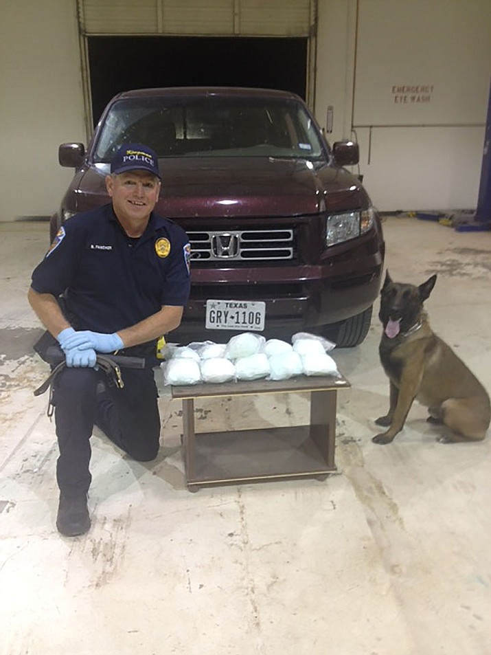 Kingman Police Department Officer Bill Fancher and K-9 Cirus display approximately 12 pounds of methamphetamine confiscated Saturday with the arrest of a suspect. The meth was inside a vehicle in a hidden compartment.