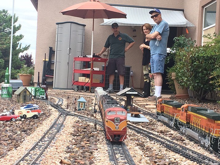 Richie Scanapico demonstrates one of his model trains for his wife and Club Event Coordinator Dick Gage.