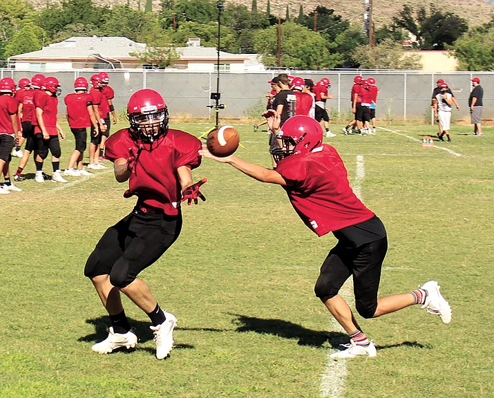 Lee Williams' David Herrera, left, hauls in a pass as Justin Sturgill tries to deny it as a defensive back during Thursday's practice at LWHS.