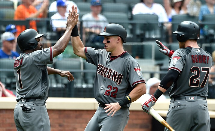 Arizona Diamondbacks' Michael Bourn (1), Jake Lamb (22) and Brandon Drury (27) high-five at home plate after Bourn and Lamb scored on an RBI by Chris Owings on Thursday in New York.
