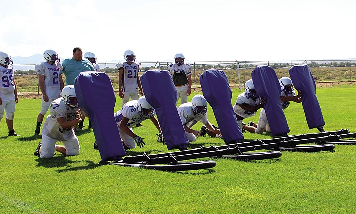 The Kingman Bulldogs linemen get work in using the 5-man sled during Friday's practice.