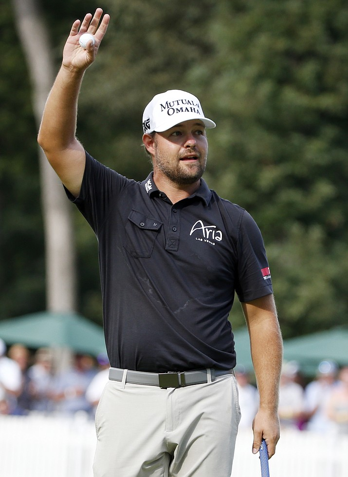 Ryan Moore waves on the 18th hole after he won the final round of the John Deere Classic golf tournament Sunday, Aug. 14, in Silvis, Ill.