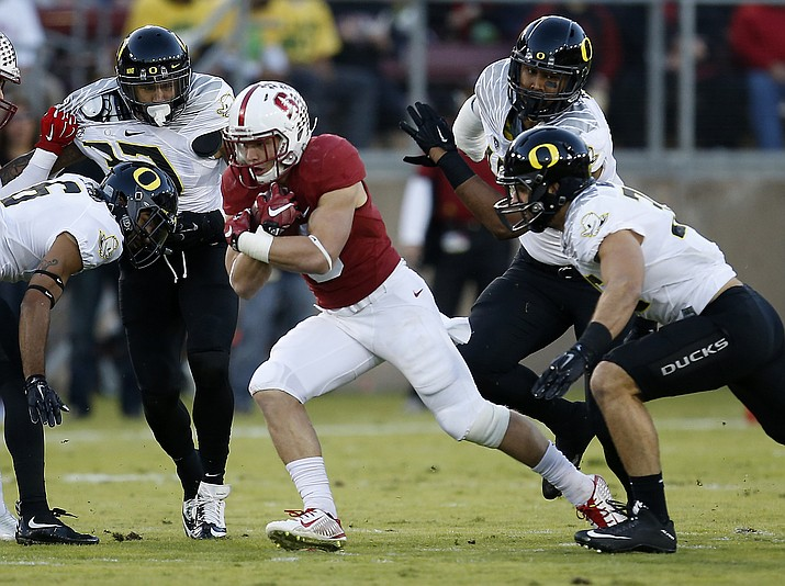 Stanford running back Christian McCaffrey (5) runs the ball past the Oregon defensive line during their Nov. 14, 2015 NCAA college football game in Stanford, Calif. The Ducks (two) and Cardinal (three) have won all the Pac-12 titles since the conference broke into divisions in 2011. The twist last season was Oregon won the head-to-head meeting and probably spoiled Stanford's playoff hopes, though the Cardinal still went on to win the conference. The two schools meet on Nov. 12, 2016.