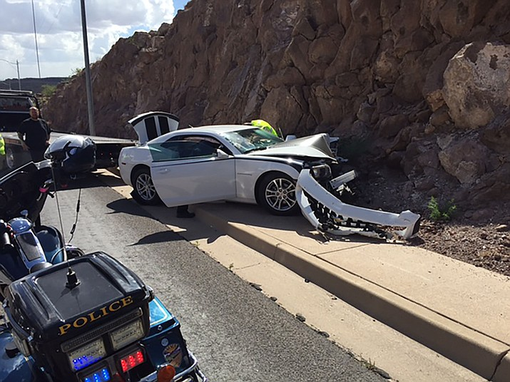 A suspected impaired driver of this Chevrolet Camaro crashed into the back of a green Dodge Journey before slamming into a light pole on Aug. 9 on Andy Devine Avenue south of the Hilltop Motel in Kingman. The investigation is ongoing, according to the Kingman Police Department.