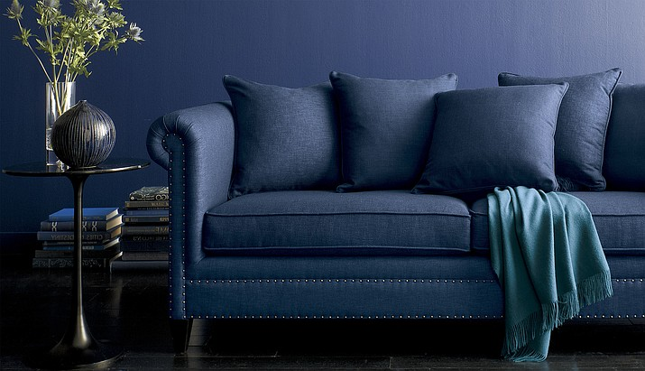 This undated photo shows a blue, upholstered sofa from Crate & Barrel. Deep, rich blues are trending across all the decor categories this fall. Furniture like this sofa in a warm navy hue bring coziness home for the cooler months.