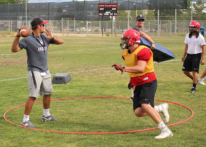 Lee Williams' All-City linebacker Edmund Ashton drills to knock the ball out of the hands of the quarterback (assistant coach Clint Sasse) during Thursday's practice.