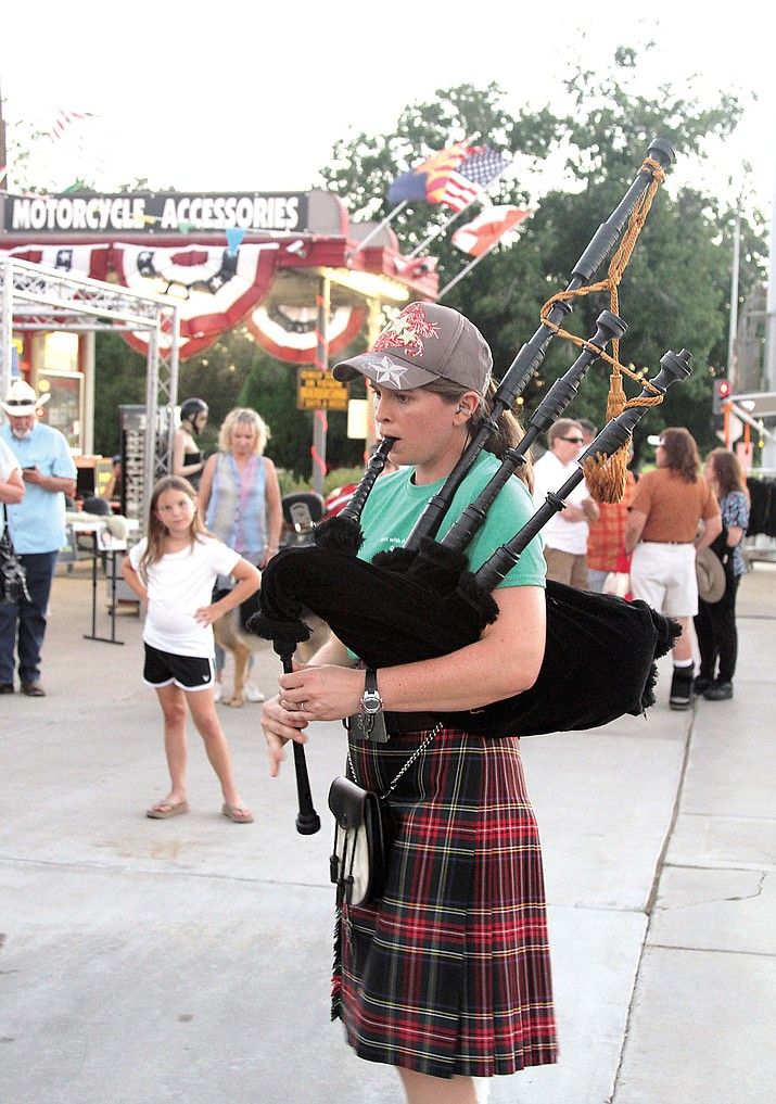 Erin Roper, Secretary for Kingman Farmers Market, plays bagpipes at the Farmers Market Saturday.