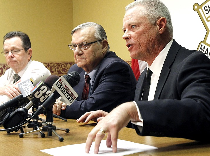 In this Dec. 5, 2011 file photo, Maricopa County Sheriff Joe Arpaio, center, listens as Chief Deputy Jerry Sheridan, right, discusses the latest in the document release on his office's handling of many sexual assault cases over the years in El Mirage, Ariz., during a news conference in Phoenix. A lawyer for the longtime sheriff of the Phoenix metropolitan area will urge a judge Friday, July 22, 2016, to recommend against a criminal contempt-of-court case for the lawman for ignoring court orders in a racial profiling case. Sheriff Arpaio and his second-in-command Sheridan were found in civil contempt two months ago for intentionally ignoring an order to stop their immigration patrols.