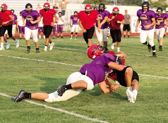 A Lee Williams receiver is on the receiving end of a Wickenburg defender's pop, which caused an audible moan from the crowd during Friday's scrimmage between the Volunteers and the Wranglers. The regular season starts this Friday for both teams.