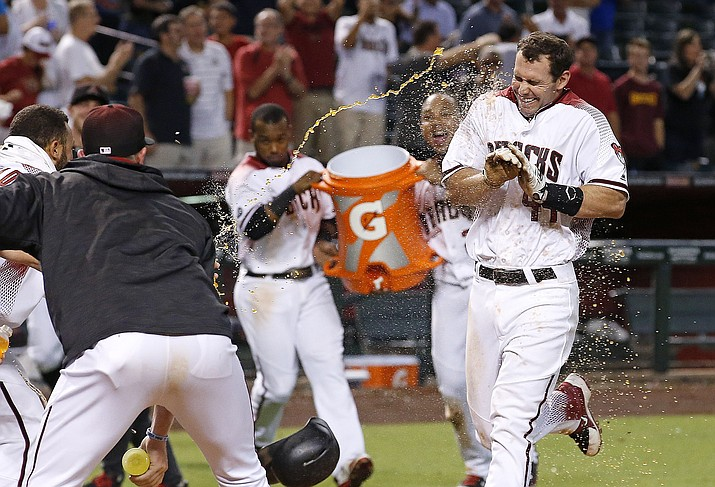 Arizona Diamondbacks' Paul Goldschmidt arrives at home plate as the team celebrates his walk off home run against the Atlanta Braves during the ninth inning of a baseball game Monday, Aug. 22, in Phoenix. The Diamondbacks defeated the Braves 9-8.