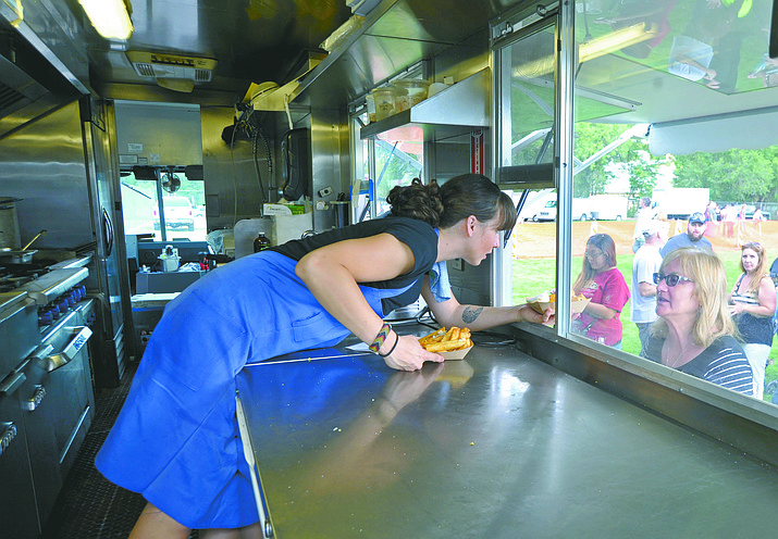 Carly Bielecki with the Frites St food truck from Phoenix hands Anne Marie Tayler a couple of orders of garlic fries during the first Prescott Food Truck Festival in 2015 at Mile High Middle School.
