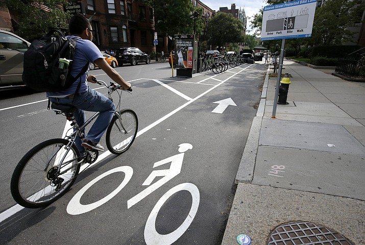 In this Tuesday, Aug. 16, photo, a cyclist enters a bike lane that is routed between parked cars and the sidewalk, right, in Boston. Chicago, New York, Boston, and other U.S. cities are reconfiguring bike lanes to make them safer in light of a spate of fatal accidents involving cyclists and cars.
