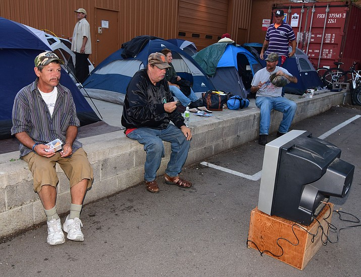 Safe Legal Sleep project campers watch a movie in the parking lot of the Coalition for Compassion and Justice Thrift Store on Fair Street Tuesday, August 23, 2016. (Les Stukenberg/The Daily Courier)
