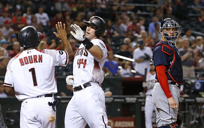 Arizona Diamondbacks' Paul Goldschmidt (44) and Michael Bourn (1) celebrate their runs scored, as Atlanta Braves' Tyler Flowers, right, looks over during the third inning of a baseball game Wednesday, Aug. 24, 2016, in Phoenix. (AP Photo/Ross D. Franklin)