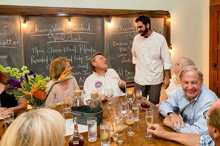 Chef John Panza (standing) speaks with guests of a pop-up dinner hosted by Senses at Groom Creek Schoolhouse in Prescott.