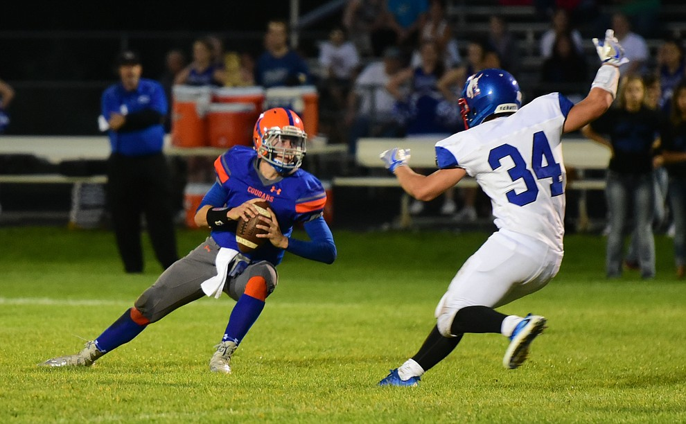 Camp Verde's Ryan Loza (34) puts pressure and sacks Chino Valley quarterback Josh Fisher (1) as the Chino Valley Cougars hosted the Camp Verde Cowboys to open the 2016 AIA football season Friday, August 26, 2016. (Les Stukenberg/PNI Photo)