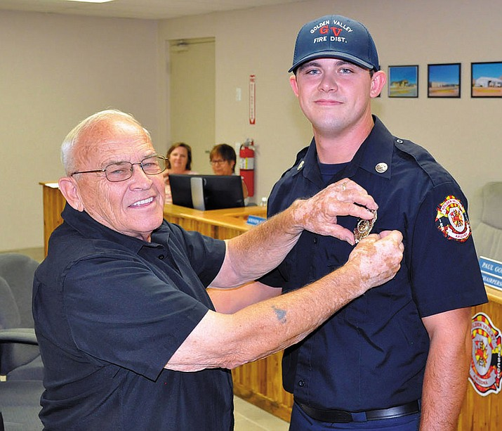 Michael Eaton proudly pins a firefighter badge on his grandson Hunter Davis during a swearing-in ceremony at the monthly Golden Valley Fire District board meeting Thursday.