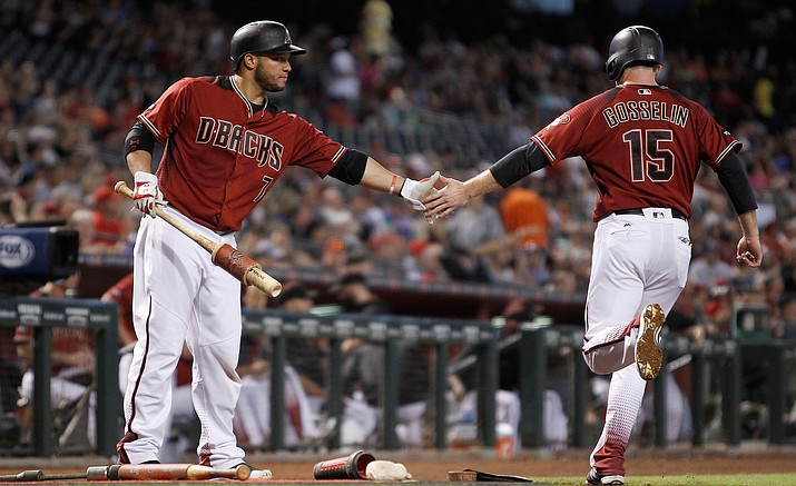 Arizona Diamondbacks' Welington Castillo congratulates teammate Phil Gosselin, who scores against the Cincinnati Reds during their baseball game Sunday, Aug. 28, in Phoenix.