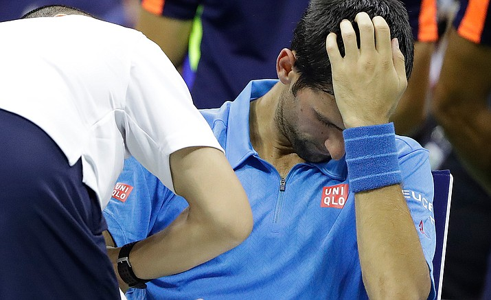 Novak Djokovic, of Serbia, gets medical attention during his first-round match against Jerzy Janowicz, of Poland, at the US Open tennis tournament, Monday, Aug. 29, in New York.